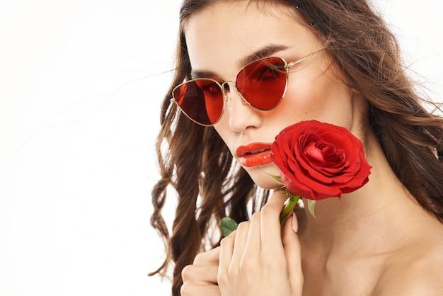 Ragazza bruna con rose rosse e occhiali da sole spalle nude.