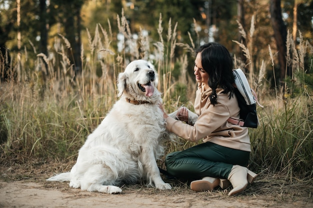 Ragazza bruna con cane golden retriever bianco sulla strada forestale