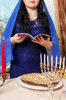 Una donna ebrea bruna con la testa coperta da un mantello blu al tavolo del seder pasquale sta leggendo la haggadah pasquale. foto verticale