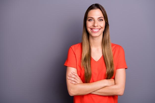 Signora bruna in maglietta rossa in posa contro il muro viola