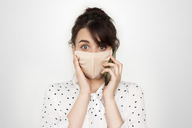Signora castana con mascherina medica sul viso parlando al telefono e abbattimento spaventoso in posa su una parete bianca dello studio