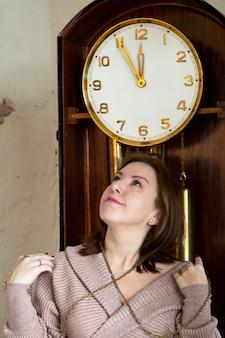Una bruna accanto a un grande orologio a pendolo. tempo di attesa.