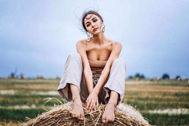 Bruna in pantaloni di lino e spalle nude seduto su balle di fieno in una calda giornata d'autunno. sguardo della donna dietro di lei c'è un campo di grano