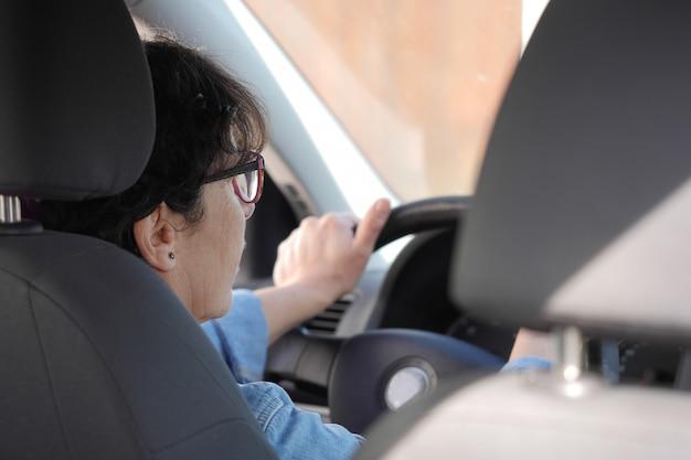 Donna matura castana che conduce automobile