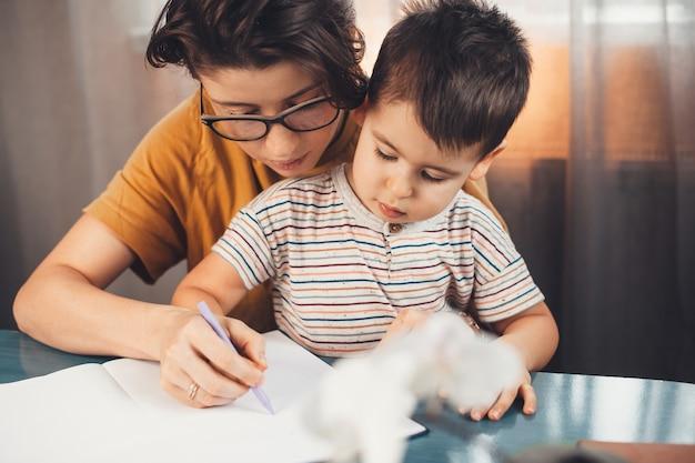La madre bruna con gli occhiali sta aiutando suo figlio a studiare e scrivere lettere in un quaderno