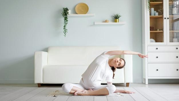 Bruna donna incinta fa piegamenti laterali sul pavimento a casa