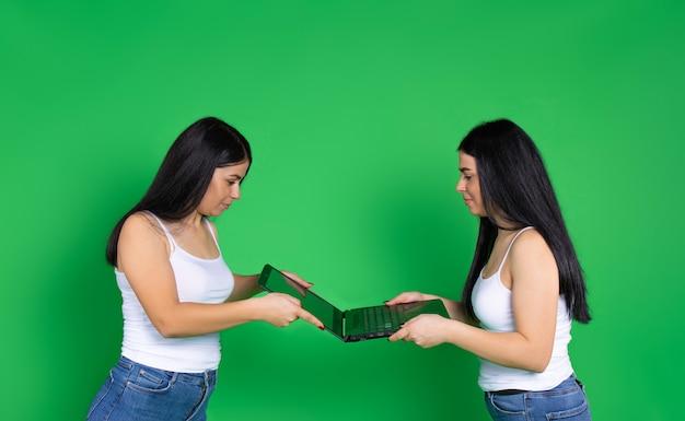 Sorelle castane condividono un dispositivo digitale portatile