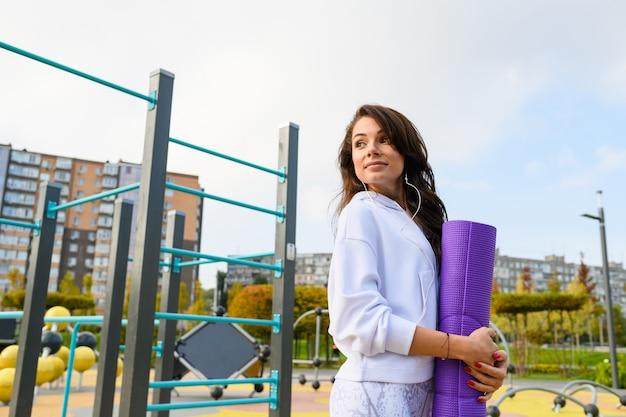 Bruna ragazza sportiva indossa cuffie, felpa con cappuccio bianca, tiene in mano un tappetino viola e posa al parco cittadino per esercizi di fitness, vista ad angolo basso
