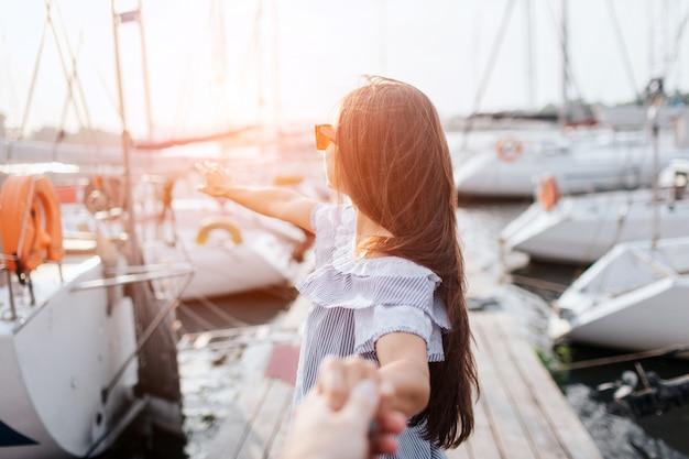 Bruna in abito a strisce si trova sul molo e tenere la mano. si guarda dietro e indica con un dito. giovane donna che indossa occhiali da sole. ci sono molti yacht su ogni lato dal molo.