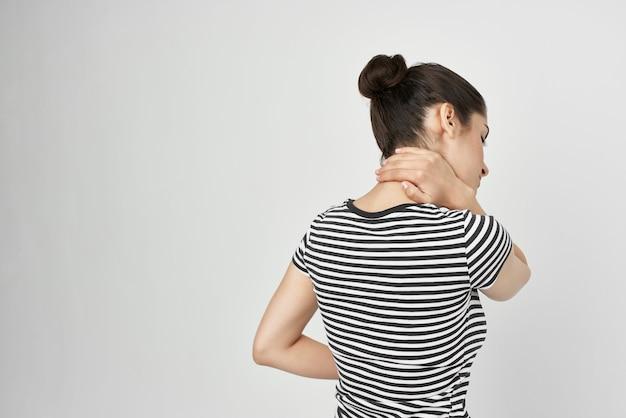Bruna con una maglietta a righe dolore allo sfondo chiaro del collo