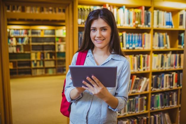 Studente castana che utilizza la sua compressa accanto agli scaffali per libri in biblioteca