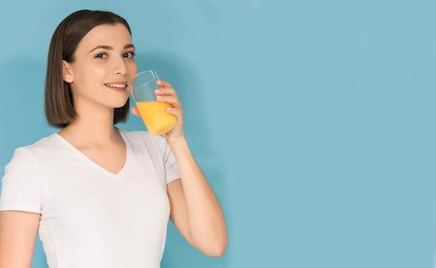 Ragazza adolescente bruna con succo d'arancia fresco