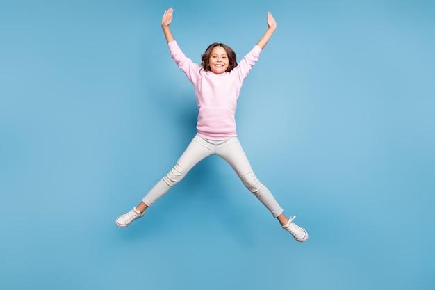 Adolescente bruna in posa contro il muro blu