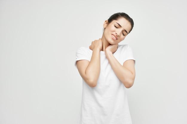 Bruna in una maglietta bianca dolore al collo problemi di salute