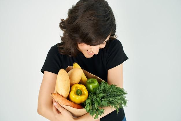 Bruna con un pacchetto di generi alimentari compiti a casa cibo sano supermercato