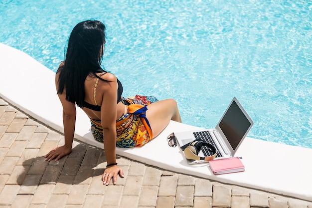 Donna castana in bikini seduta sul bordo della piscina con i piedi nell'acqua accanto al suo computer portatile che si rilassa durante le vacanze estive.