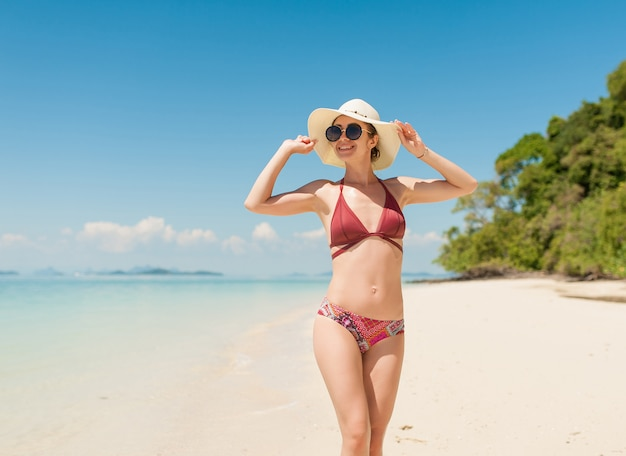 Donna castana in occhiali da sole del bikini di borgogna sulla spiaggia tropicale del fondo e sull'acqua di mare blu