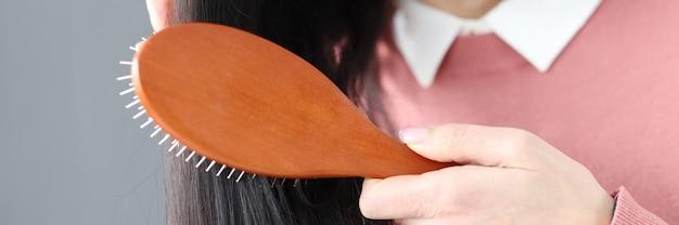 La donna castana si pettina i capelli con il concetto adeguato di cura dei capelli del pettine di legno