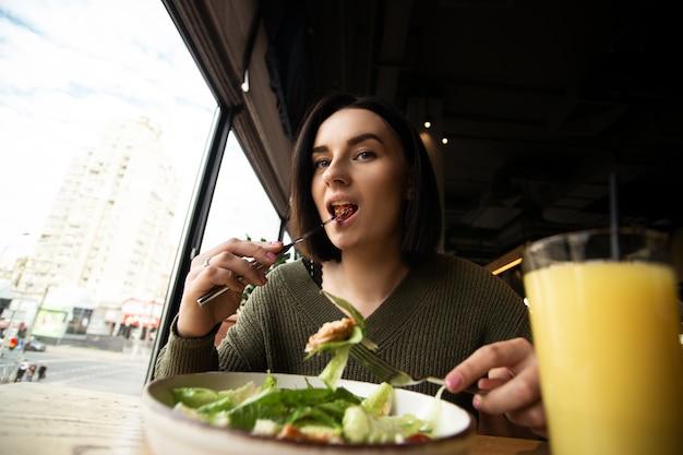 Donna castana che mangia insalata caesar con piacere. vetro sfocato di succo d'arancia fresco sul davanti.