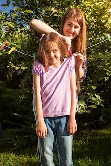 Donna castana che appende ragazza su stendibiancheria in giardino