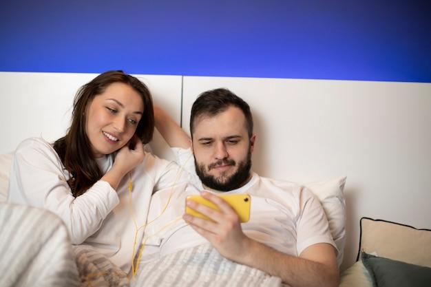Donna castana e il suo ragazzo barbuto guardando smartphone