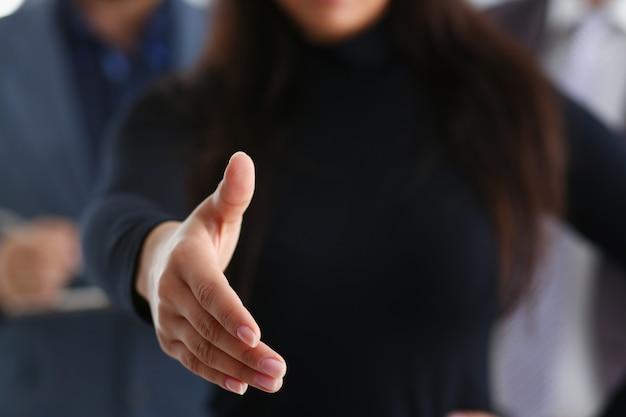 Donna castana che offre la mano da stringere