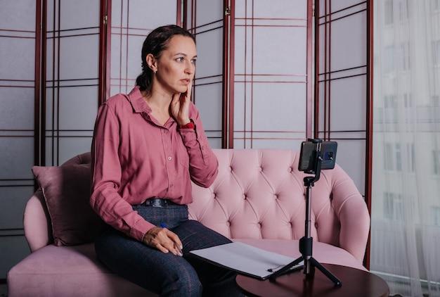 Una donna bruna in abiti da ufficio conduce una consultazione online a casa