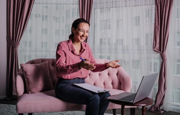Una donna bruna in abiti da ufficio conduce una consultazione online con un telefono a casa