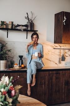 Donna castana in pigiama che mangia pasticcini in cucina
