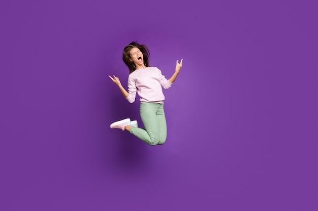 Donna castana in maglione pastello che posa contro il muro viola