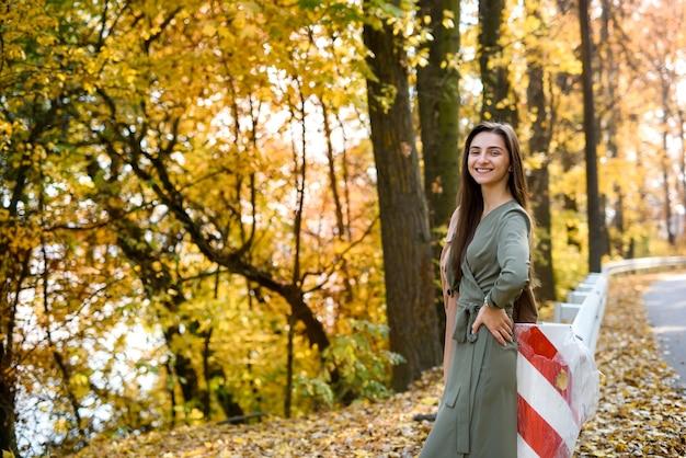 Ritratto di donna bruna in autunno parco che indossa un abito oliva