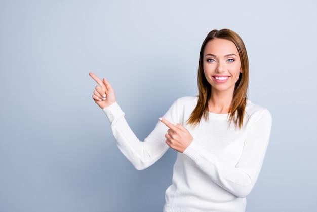 Donna castana che posa contro il muro azzurro
