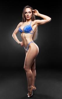 Donna bruna in posa in un bikini blu