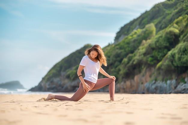 Donna castana a praticare yoga da solo in spiaggia. indossare una maglietta bianca. è scalza. è contro il cielo blu