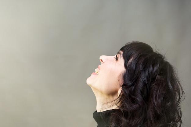 Donna castana nel profilo su un fondo grigio. capelli corti neri.