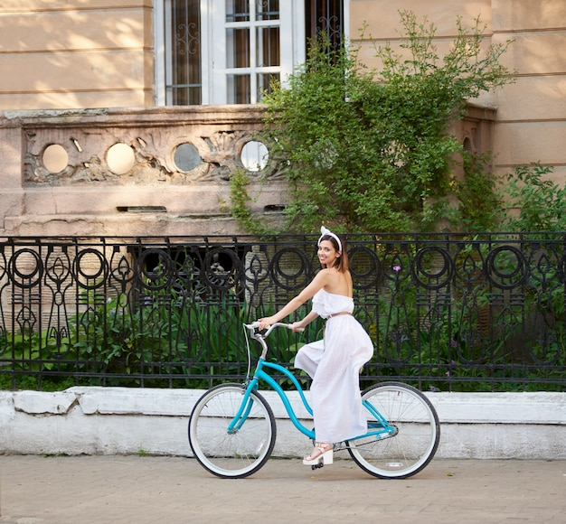 Donna castana che guida bici blu d'annata