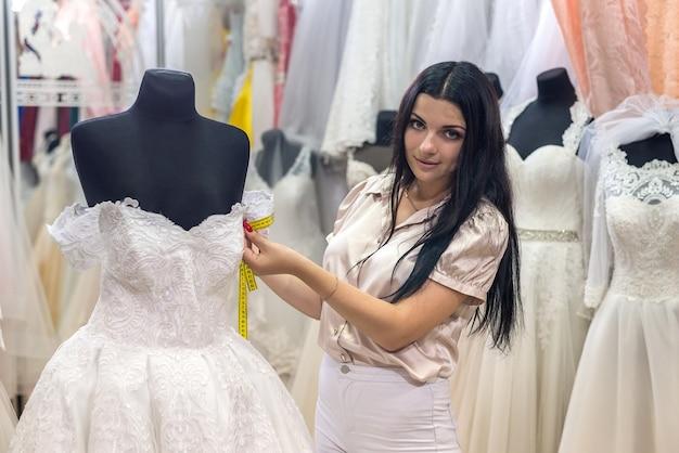 Venditore di donna bruna che misura i dettagli dell'abito da sposa