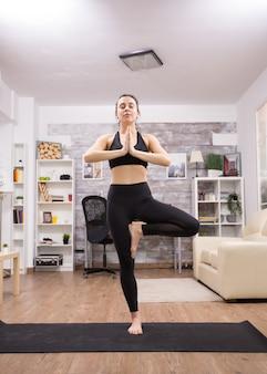 Donna castana che sorride mentre fa la posa di yoga che sta in una gamba.