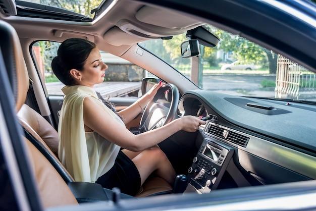 Donna castana che avvia il motore in macchina con la chiave