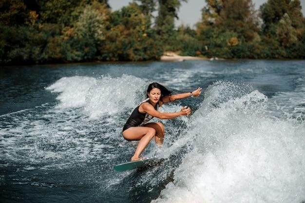 Donna castana che pratica il surfing a bordo giù l'acqua blu