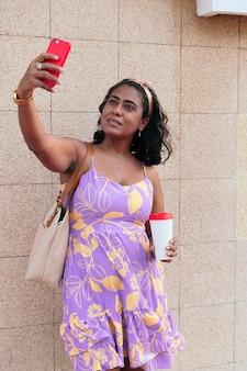 Donna castana che si fa un selfie con il suo smartphone e una tazza di caffè per strada