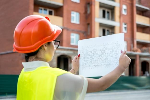 Donna castana in uniforme che esamina la pianta dell'edificio