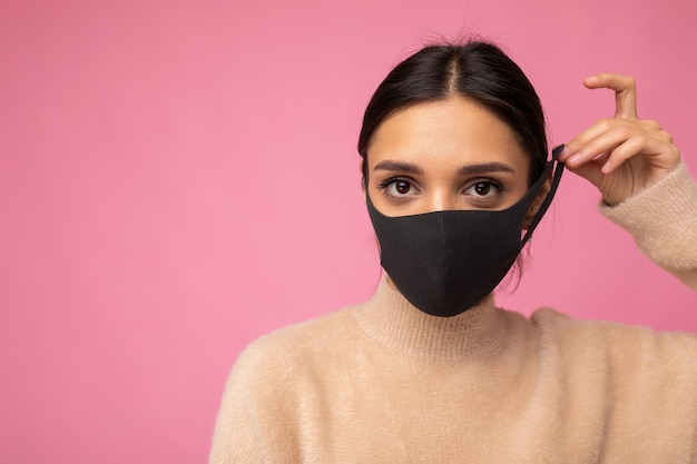 Donna bruna che indossa una maschera di protezione antivirus per prevenire l'infezione da corona covid-19 e sars cov 2 isolata su sfondo rosa. copia spazio