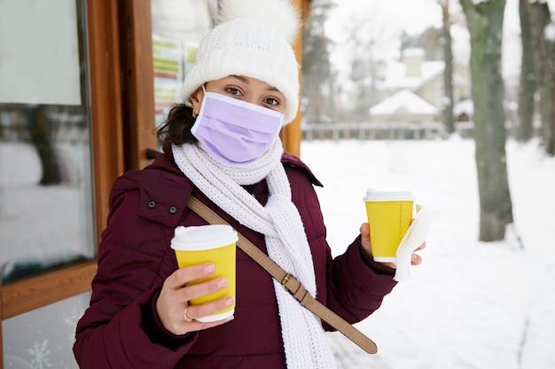 Donna castana che indossa la mascherina medica che tiene due tazze gialle da asporto di caffè o tè. pausa caffè concetto di tempo in un inverno nevoso giorno