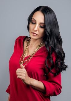 Donna castana che indossa una camicia rossa e tiene in mano una catena d'oro