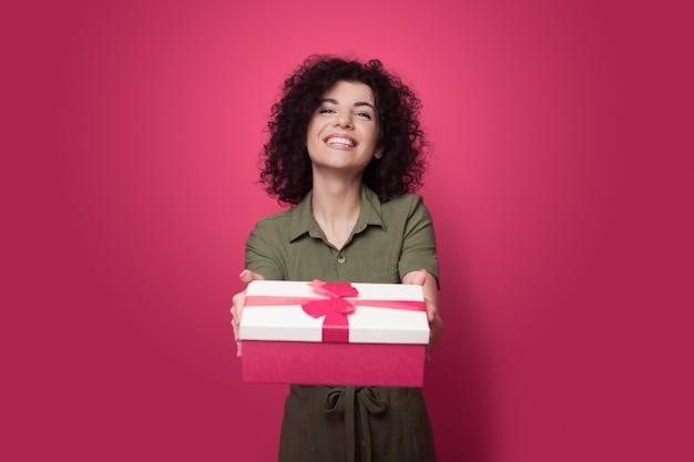 La donna castana con i capelli ricci sta dando un regalo alla macchina fotografica essendo molto felice e generosa su una parete rossa dello studio durante le vacanze
