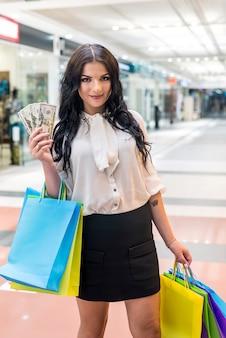 Donna castana con il fan del dollaro che fa acquisto