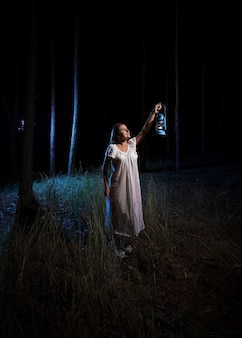 Donna bruna con lanterna a gas che illumina la foresta di notte