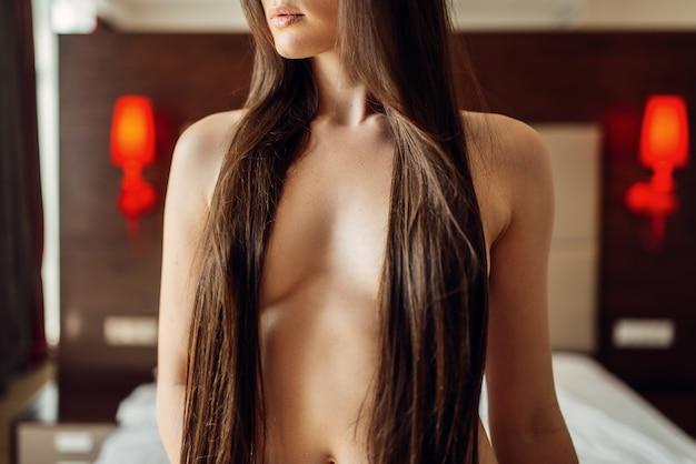 Donna castana con capelli lunghi e seni nudi
