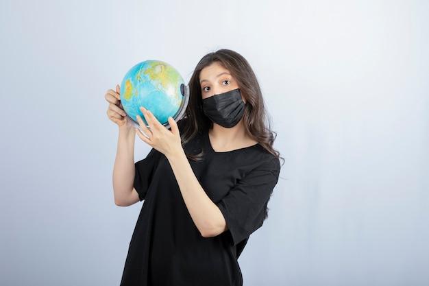 Donna castana con capelli lunghi nella mascherina medica che tiene il globo del mondo.